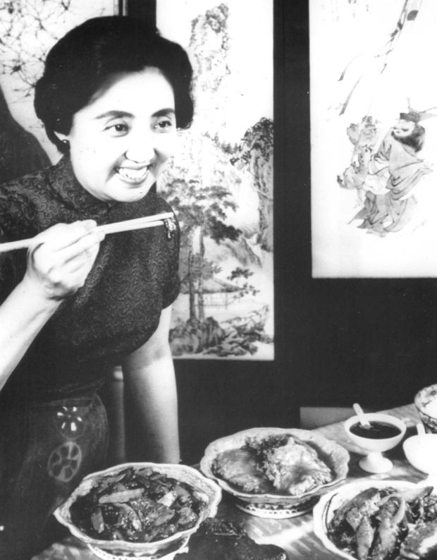 A black and white photo of an Asian woman with a neat bob, smiling to someone off-camera to the right, holding up a bite of food between two chopsticks. An ornamental screen with cranes sits in the background.