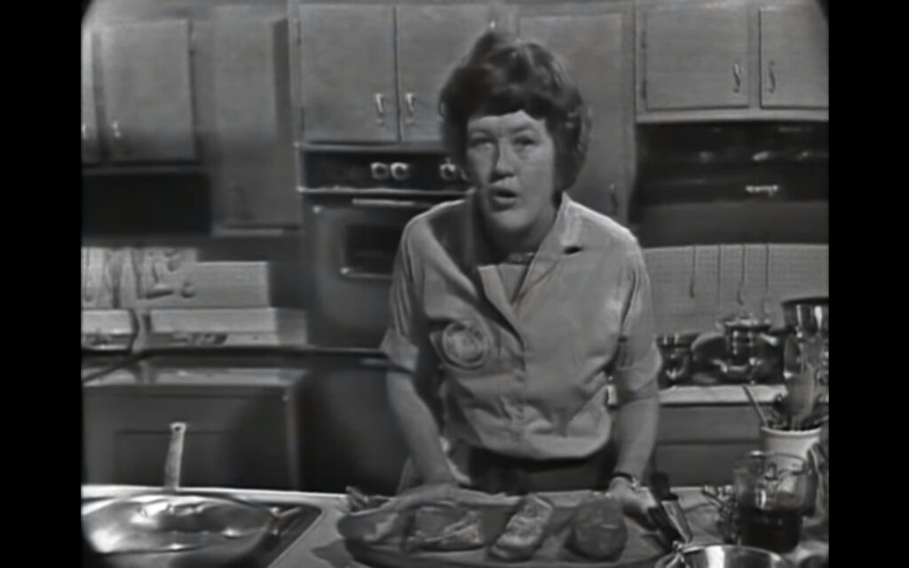 A black and white image of Julia Child, curly hair cropped at her neck, leaning forward towards the camera over a cutting board with several cuts of beef.