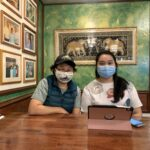 Two Asian women, one middle aged and one young, sit next to each other at a wooden table, both wearing masks. Behind them is an ornate Thai embroidered artwork featuring two elephants. On the wall to the left are rows of photos featuring the restaurant's clientele over the years.