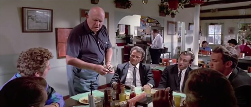 A screenshot of the tipping scene in Reservoir Dogs, where Joe is picking up the pooled tips from the table and asking who didn't contribute.