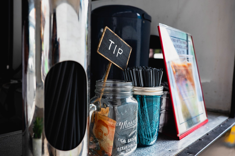 "An angled shot of a coffee shop counter, with swizzle sticks and a straw dispenser flanking a glass jar with some cash inside. A small sign sticking out of the glass jar reads ""TIP"""