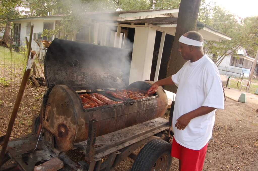 An African American man in a white tshirt, red shorts and white sweatband carefully tends to meat on a smoky cooker, all under a canopy of green trees.