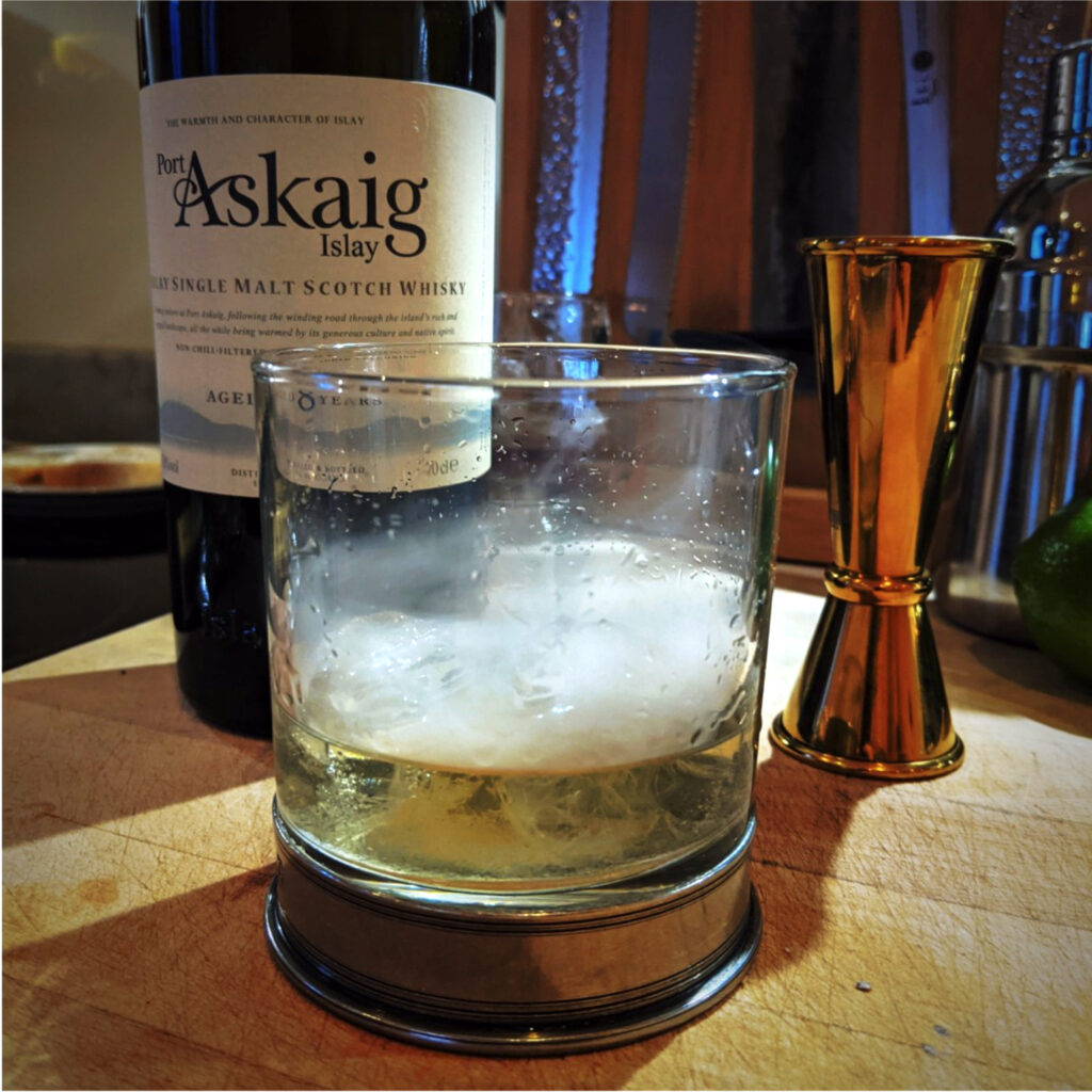 A lowball glass in the foreground shimmers with faint smoke rising off the surface. A bottle of Askaig Islay whisky and a copper jigger are visible in the background.