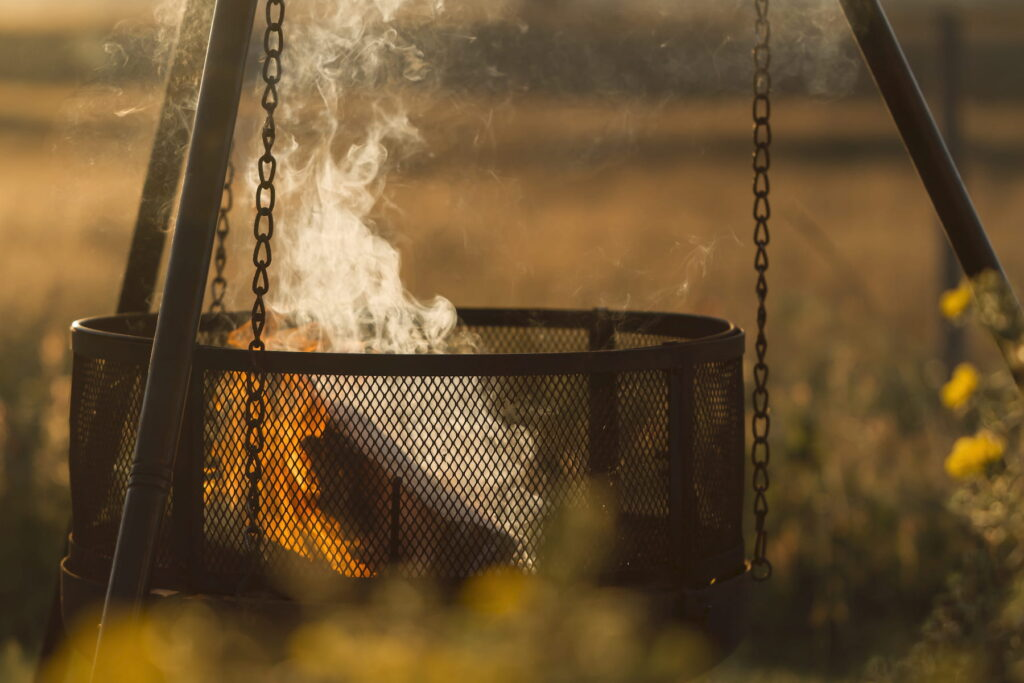 Smoke rises from a few logs that are burning in a metal basket, suspended by metal chains from a tripod. The light is golden and the smoke is a wispy curly white, set against a golden meadow.