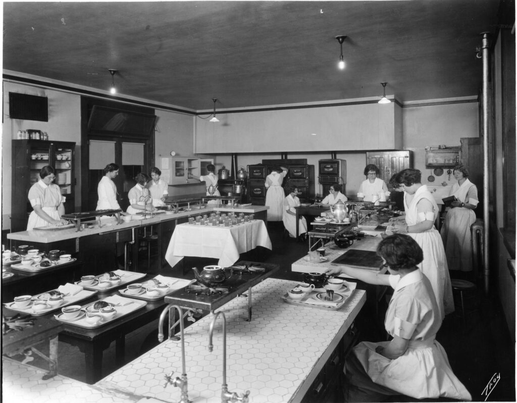 A black and white photo featuring around 10 young women scattered throughout a room that has long white tables with various meal place settings on them, and cupboards along the walls.