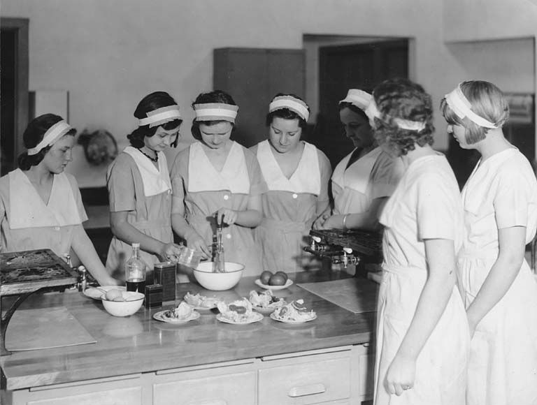 A black a white photo featuring 7 young women with pale faces and dark hair held back with white headbands, all wearing matching dresses with white pinafores. They're standing around a kitchen island watching two of the girls whisking ingredients in a mixing bowl.