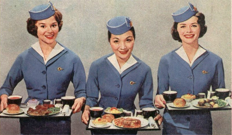 Three smiling stewardesses, all in pale blue uniforms with dark hair pulled back beneath trim little pillbox hats, hold up trays of airline food and smile
