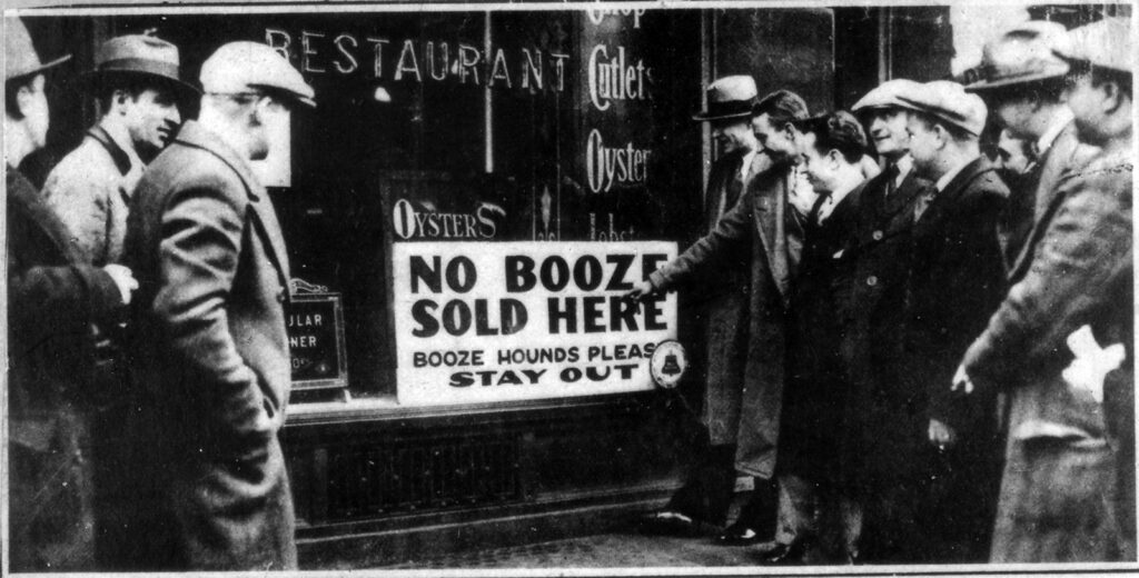 """A black and white photo of several men smiling and pointing to a sign in a shop window that reads """"No booze sold here: Booze hounds please stay out"""""""