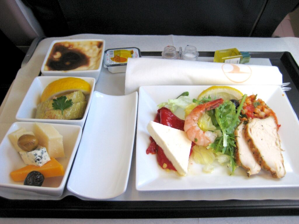 Photograph of a meal on a airplane tray featuring some slices of chicken breast, a shrimp, and a piece of cheese on salad, some small dishes to the side with fruit and other sides, and a tiny salt and pepper shaker at the top