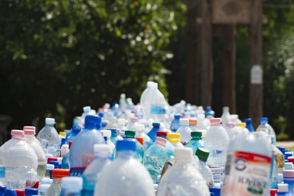 A table full of water bottles, maybe several dozen, with a few in focus, cropped to feature their upper halves. There are green trees in the background.