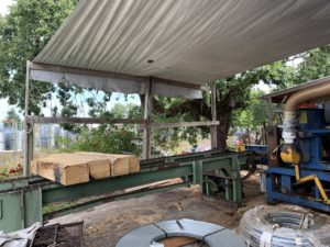 Four pieces of lumber sit on a green metal conveyer belt in an outdoor workshop under a tin roof. A tree shades one corner of the structure.