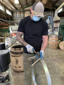 A tall white man in a baseball cap and blue face masks shows us a metal barrel hoop