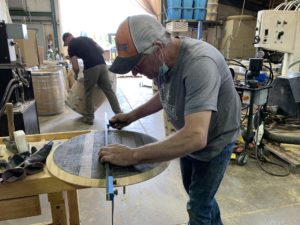 A man in an orange and gray cap carefully measures a slatted round wooden barrel top