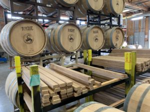 Stacks of barrels with a bearded man's face printed on one end. Stacks of lumber are visible in the foreground.