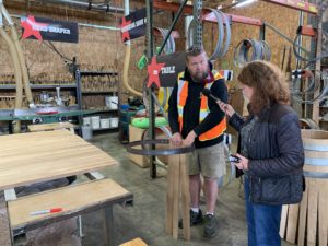 Cynthia holds up a mic to a tall, bearded white man wearing an orange safety vest. He is holding a few staves together on the inside of a metal hoop, demonstrating how it will all fit together.