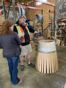 Cynthia holds a mic up to Nick while he holds one hand up over an unfinished barrel - three hoops hold the staves together at the top, which then fan outward at the bottom like a skirt or a teepee.