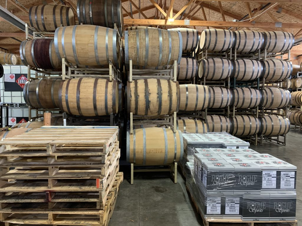 Dozens of barrels sit in three vertical rows in a timber-roofed warehouse. Pallets of Rogue products are visible in the foreground.