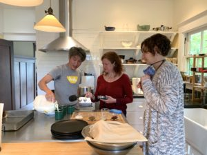 """Minh, a slim Asian man with gray hair, wearing a gray tshirt that reads """"Hodo,"""" pour creamy soy milk from a gallon milk jug into mugs while Cynthia and Nicky look on. They are in a modern kitchen with hanging pendant lights overhead."""