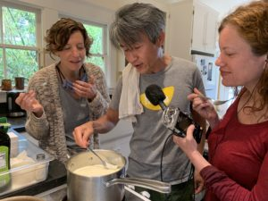 Minh carefully lifts a thin film of tofu skin (or yuba) out of a silver pot of soy milk heating on the stove, while Cynthia and Nicky lean over to observe