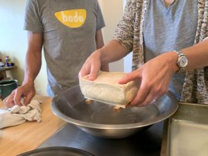 Close up of Nicky holding a newly formed block of tofu over a mixing bowl of water