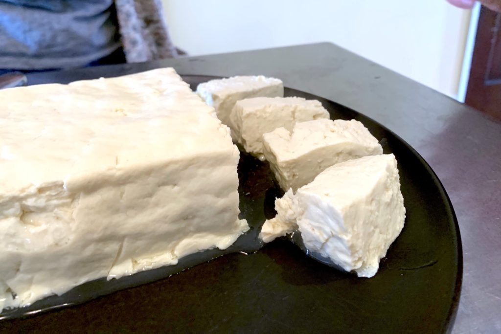 A block of white tofu, slightly imperfect, sits on a black plate with a few small cut cubes on one side of the plate.