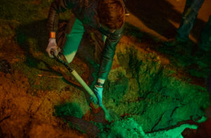 Overhead shot of a man with dark hair, wearing a black jacket and work gloves, shoveling dirt out of a 3 foot diameter hole under the glow of green lights. It's night and very dark outside.