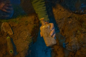 A man's hand holds a small, dirt-encrusted glass bottle with a narrow neck over a hole dug into the ground.
